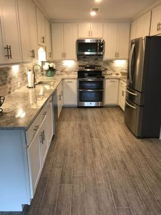 White and gray kitchen, White Bahamas granite, marble back splash with  lowered outlets. Wood grain porcelain tile plank floor. http://www.simplify-organize.com/kitchen-renovation