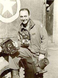 U.S. Army photographer attached with the 3rd Infantry Division/ 3rd Signal Company, Staff Sgt. William Heller holds his 4x5 Anniversary Speed Graphic camera, along with a Graflex K-20 aerial camera and around his neck an Argus C-3 'brick' camera.