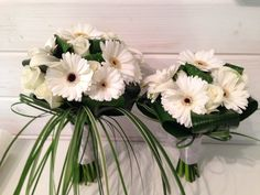 A hand tied bouquet using roses and gerbera with rolled tropical leaves and an extension of trailing grasses on the brides bouquet.