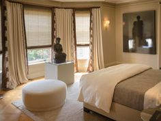 Neutral textiles create a serene environment in this master bedroom. Cream-colored curtains and textured shades block harsh light from the bay windows, while a large Buddha statue anchors the room in a zen-like ambiance.
