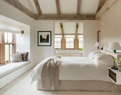 """The master bedroom is scaled for two, and connects the couple with the surrounding land. The custom slip covered bed and natural lines """"are never supposed to look perfect."""""""