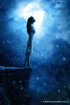 Dream in the enchanted night woman standing on cliffs edge blue night sky, light