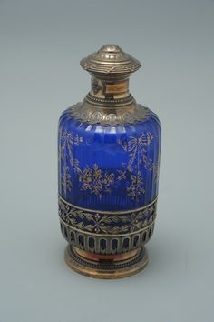 Perfume bottle - Paneled cobalt blue glass with gold tracery and fitted with a gilded silver frame top and cover, glass stopper. Purity mark of Minerva head and unknown maker's mark of GB. Lalique Perfume Bottle, Blue Perfume, Antique Perfume Bottles, Vintage Perfume Bottles, Beautiful Perfume, Art Nouveau, Bottle Vase, Bottles And Jars, Perfumes Vintage