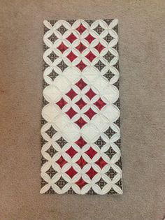Cathedral windows Table Runner. I think I would simplify this instead of an actual quilt.  but this kind of pattern would go well with the curtains in the dining room.