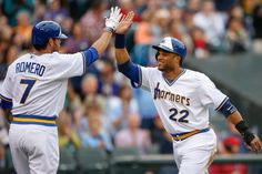 Robinson Cano #22 of the Seattle Mariners is congratulated by Stefen Romero #7 after scoring on a throwing error by Marc Krauss of the Houst...