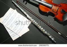 Violin and flute with music notes on dark background - stock photo