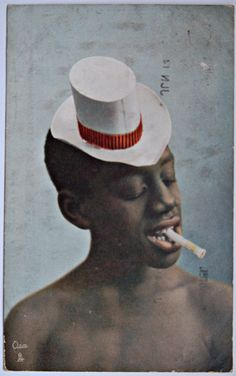 1914 Tucks Oilette Ful Dress in Dahomey Boy in White Hat with Red Band and Unlit Cigarette