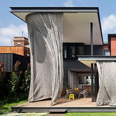 Australian architect Matt Gibson and his studio have renovated and extended a traditional villa in Melbourne, adding deep verandahs that can be protected from harsh sunlight using woven steel-mesh curtains.