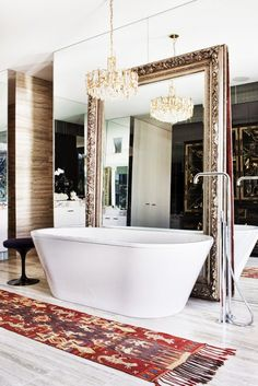 A mirror behind the bathe will visually enlarge a space. A current trend is to display bathroom and accent mirrors over other mirrored surfaces. This layered, luxe look adds character to any space, and is a great option for renters or homeowners looking to modernize an inherited dated mirrored wall.
