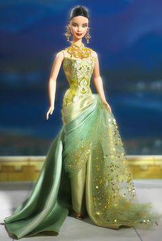 Exotic Beauty™ Barbie® doll wears a gown of green satin with a strapless golden and green jacquard bodice. The skirt is draped to one side and layered with golden glitter encrusted green tulle. Her black hair is pulled back in a low chignon, and golden dangling earrings and necklace enhance her tan skin.