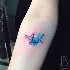 Tatuaje de una grulla de origami con un fondo de acuarela de...