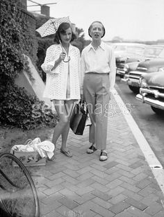 Diana Vreeland  Cordelia Robertson In Southampton    : French-born American fashion editor Diana Vreeland (1906 - 1989) (right) and socialite Cordelia Robertson (1900 - 1984), both dressed casually, stand on the street probably in front of the Southampton Bathing Corporation, Southampton, New York, 1940s. Robertson holds a parasol to shield her head from the sun.