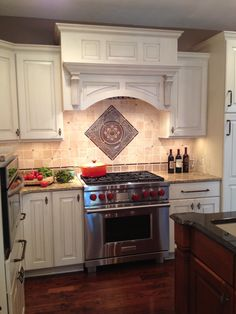 Powell Ohio kitchen remodel features a tumbled stone backsplash with Sonoma Tilemakers medallion and deco stripe accents over a Wolf Range.  Designed by Monica Miller, CKD, CBD, CR of J.S. Brown & Co.