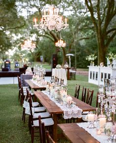 Lovely outdoor reception setting with elegant hanging chandeliers, lanterns and flowers for centerpieces, and lace table runners on wood tables. Pretty!