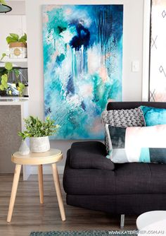 Modern Australian living room with grey couch and scandinavian style furniture. Styled with adairs cushions. Original abstract artwork in indigo blue and green by Australian artist Kate Fisher.