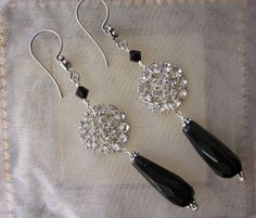 "The rhinestone center of these earrings used to be a button before becoming part of this design. The button loop has been removed from the back and filed smooth.  he earrings are long hanging 3 3/8"" from the top of the curved ear wire to the end of the jet black glass bead. They measure 3/4"" across at the rhinestone/pearl accent."