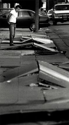A resident looks at a buckled sidewalks in the Marina District of San Francisco after the 1989 Loma Prieta earthquake.
