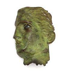 Torben Hardenberg: A brooch of partly green copper in the shape of a face. L. app. 7 cm. Circa 1990.  Torben Hardenberg, b. Frederiksberg 1949