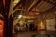 Huge gathered fairy light canopy running down the barn at Lillibrooke Manor, with warm gold uplighting. Sparkly!