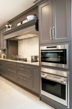 Amazing gray kitchen design with kitchen cabinets painted gray and granite countertops.