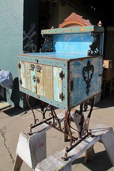 Small whimsical blue cabinet was made from old handmade ice box, found at Urban Ore in Berkeley. Vintage wrought iron base, victorian cast iron hardware. Crest is from deconstructed victorian furniture piece. Carved oak embellishments on the sides are from an antique piano