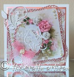 A beautifully hand crafted wedding card approx 145mm square created in the shabby chic style and comes with a tissue lined coordinating white presentation box. White matt card stock has been layered with dusky pink mirror card and shabby chic style rose design backing papers. Genuine cream lace, faux pearls and mulberry paper florals all come together with die cut swirls, organdie bow and butterflies to create a card that has dimension and a luxurious quality that will delight the happy…