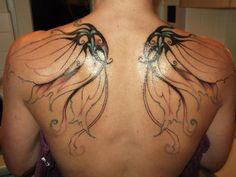 Elegant black-and blue fairy wings tattoo for women on back