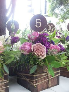 Love this wooden box arrangement filled with flowers in shades of purple and pink accented with greenery. It makes a beautiful rustic yet classy centerpiece. Placing number picks in each is a great way to display your table numbers! | Design By: Flour and Flower Designs | followpics.co