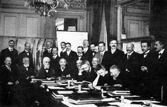 At First Solvay Conference (1911), Curie (seated, second from right) confers with Henri Poincaré; standing, fourth from right, is Rutherford; second from right, Einstein; far right, Paul Langevin