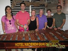 Guided tour group posing with a marimba instrument at Hacienda Guachipelin while on their Costa Rican Getaway.... See more at: https://costaricamonkeytours.com/costa-rica-tour-131/