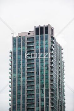 image of a tall office building. - Distant view of a tall commercial building against sky.