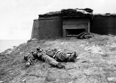 The corpse of a German soldier, in front of a bunker overlooking the coast, June 1944. (Regional Council of Basse-Normandie/U.S. National Ar...