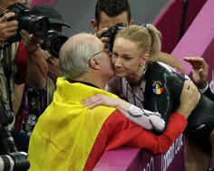 Romania's gymnast Sandra Raluca Izbasa hugs an unidentified person after she won the gold medal for the artistic gymnastics women's vault final at the 2012 Summer Olympics, Sunday, Aug. 5, 2012, in London.