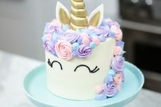An easy funfetti Unicorn Cake recipe adorned in pastel buttercream and topped with a golden horn will bring magic to any occasion!