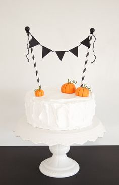 Dress-up a plain cake for Halloween using black triangles for the bunting, black & white patterned paper straws and little marzipan pumpkins (store bought or hand made).