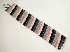 I really like rose with black and gray! Ive used matte black, hematite, soft gray, rose and pale blush Delicas in a slanted stripe pattern for this cuff.  The cuff measures 7 1/2 (19.1cm) long and 1 3/8 (3.6cm) wide with a beaded toggle and loop closure. Did you know that well-made beadwoven pieces can be very durable as evidenced by highly-valued vintage beadwork available in the antiques market? Given the same care you take with your fine jewelry, bead woven pieces can last a life...