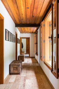 Decoração de casa de campo com madeira. No corredor caixas de madeira, janela de madeira, portas de madeira, teto de madeira, piso de madeira e quadros.