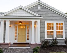 love the color of grey exterior with the white trim and the yellow door