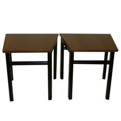 Pair of side tables with black legs ending with original black leather anklets and asymmetrical walnut tops. The length of the back is 22 inches