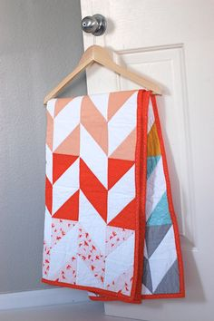 modern baby quilt, gender neutral color, herringbone pattern in gray, mustard, teal, peach, and red.