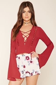 A crop top featuring long trumpet sleeves, a plunging lace-up neckline, cutouts along the front and sleeves, and an invisible zipper on the side.