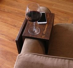 Handmade arm rest tray table with side storage slot for magazines. The perfect addition to a sofa in any home, apartment, condo, or man cave. It has been sanded down, then stained and sealed with a dark walnut finish. This piece does not include the accessory items as shown in the
