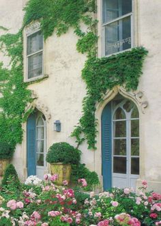 French cottage with greenery on the walls and flowers in the garden