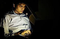 Portrait of a guy working in the dark. Face lighted up by his laptop screen.