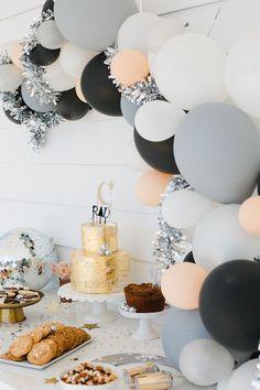Decora la Fiesta con globos blancos, negros, grises color melón; agrega una escarcha plateada y un lindo pastel dorado