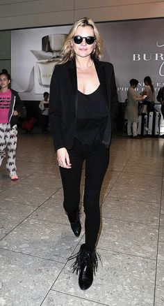 Kate Moss wears a black top, skinny jeans, a blazer, and black fringe boots