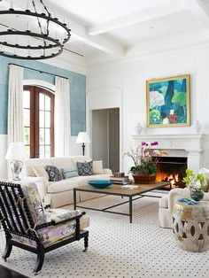 This beautiful painting adds so much color and life to this room, would love to know who the artist is. The room's blue accent colors picked up from the painting helps to move your eye around the very neutral room.   BHG - Pattern Partners