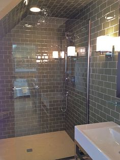 Angled roofline for shower.   Fabulous Sagebrush green glass tile shower!