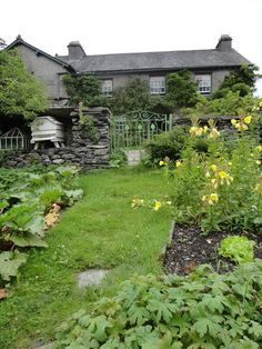 View of Beatrix Potter's Hill Top House from the garden, through the green wrought iron gate. Near Sawrey, Cumbria Lake District, England, UK