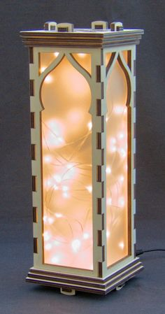 Download the laser cutter files to make your own LED light string lamp. All four sides are decorated with a Moroccan style window opening and the top is decorated in the style of a Moroccan screen.